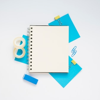 Top view of blank notebook over blue supplies