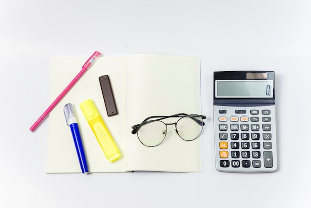 Top view blank notebook  glasses one notebook and pen, liquid side calculator on white background.