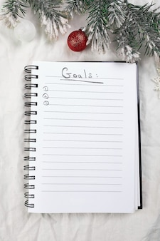 Top view of blank notebook for goals resolutions and christmas decoration on white textile linen