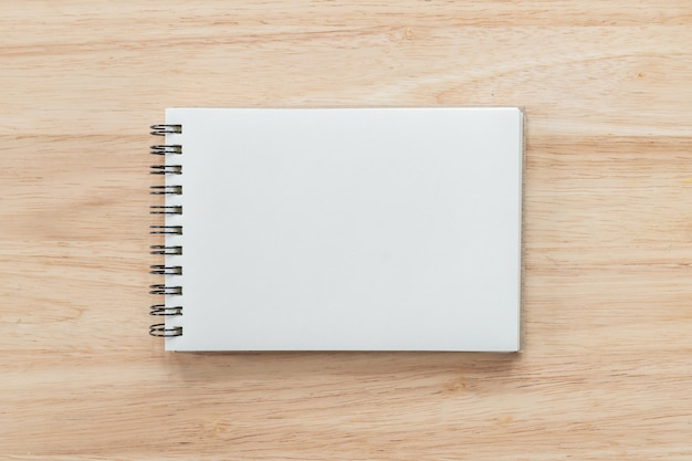 Top view of blank notebook and natural light on wooden table.