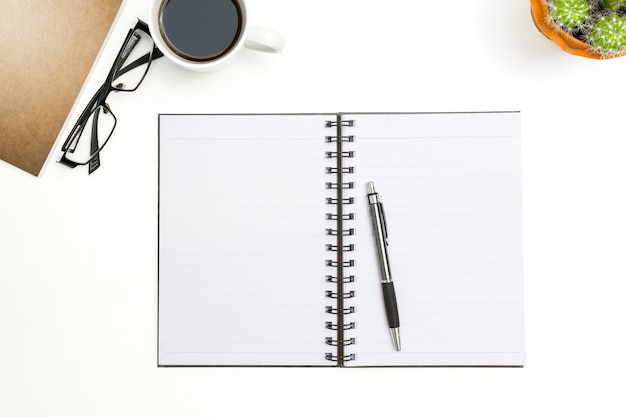Top view blank notebook, pen and glasses on white desk background