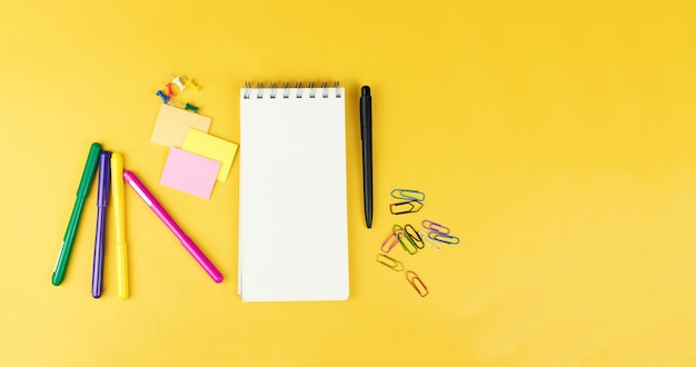Top view of blank notebook and school supplies like colored markers, sticker and clipers on yellow background, space for text