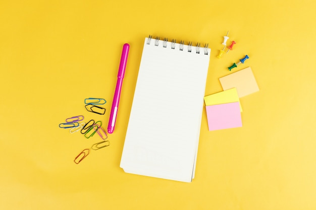 Top view of blank notebook and school supplies like colored markers, sticker and clipers on yellow background.