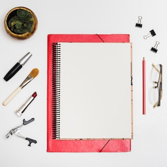 Top view of blank notebook with cosmetic products; paper clips; pencil; eyeglass over white desk