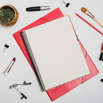 Top view of blank notebook with cosmetic products; paper clips; pencil over white desk
