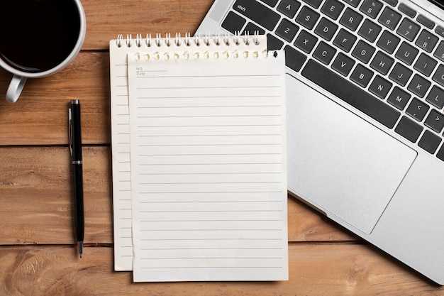 Top view blank notebook with lapto on wooden office table