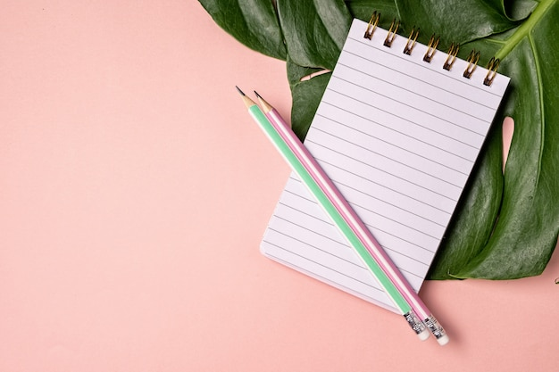Top view of blank notebook with pen and monstera lief on pink pastel background with copy space