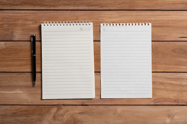Top view blank notebook with pen on wooden office table