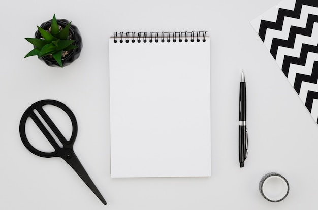 Top view of blank notebook with scissors and plant