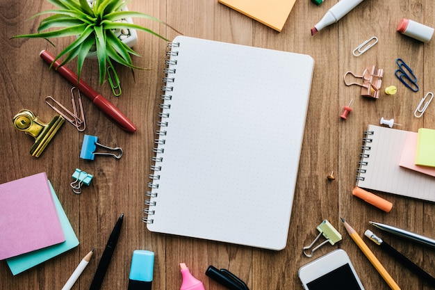 Top view of blank notepad and office supplies on wood background