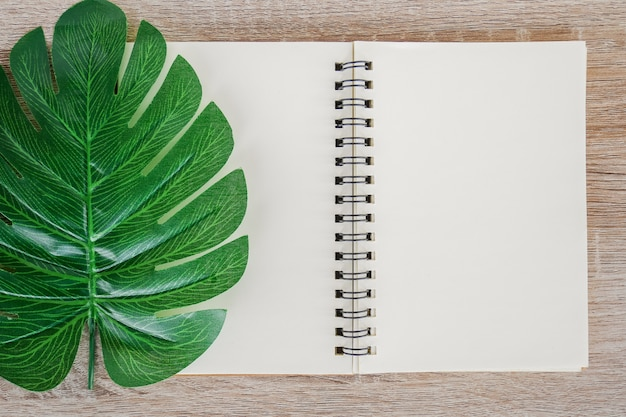 Top view of blank open notebook on wooden desk background with green tropical monstera leaves.