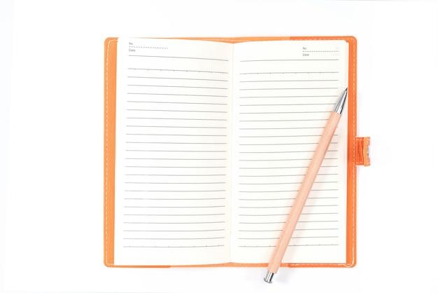 Вид сверху пустой оранжевый кожаный дневник и карандаш на белом столе