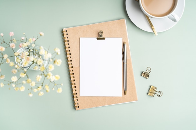 Top view blank paper notebook, flowers, golden paper binder clips, cup of coffee and pen. flat lay