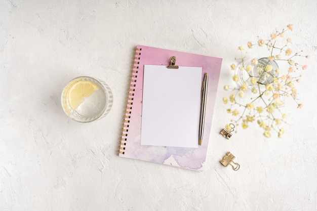 Top view blank paper notebook, flowers, golden paper binder clips, water with lemon and pen.  flat lay