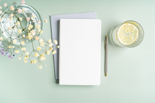 Top view blank paper notebook, flowers, water with lemon and pen. flat lay