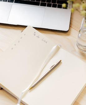 Top view blank paper notebook with to do list, flowers, laptop keyboard, cup of coffee and pen.