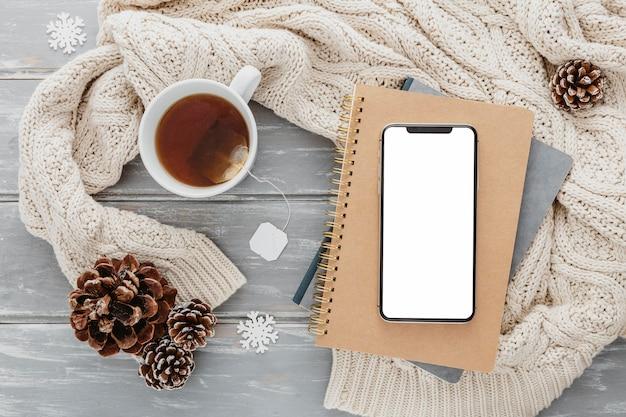 Top view blank phone on agendas with tea mug