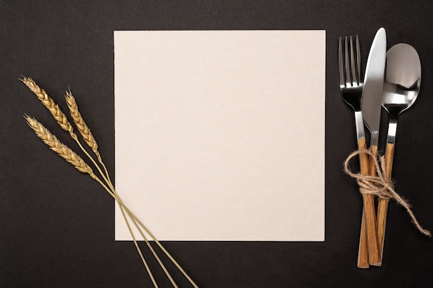 Top view blank recipe paper page, card and cutlery on black