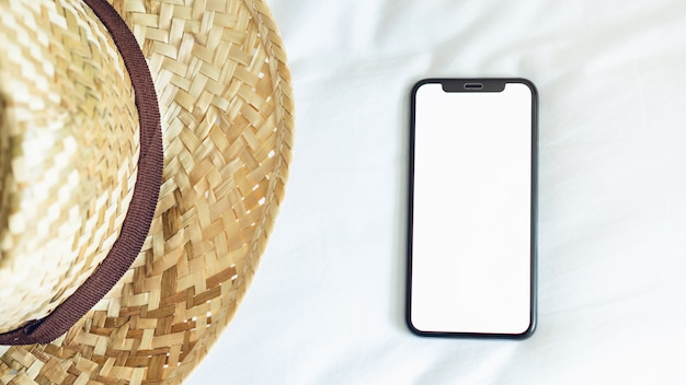 Top view blank screen of smartphone on room and hat, during leisure time.