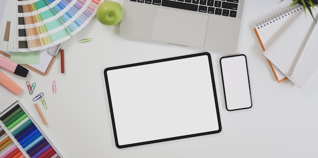 Top view of blank screen smartphone and tablet in modern designer workplace