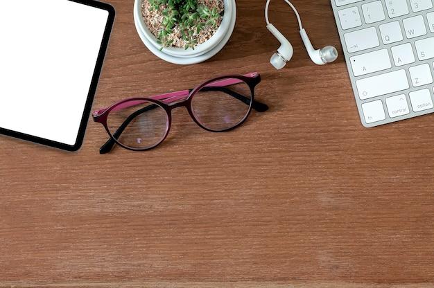 Вид сверху пустой экран планшета, компьютерной клавиатуры, очков и наушников на деревянной поверхности