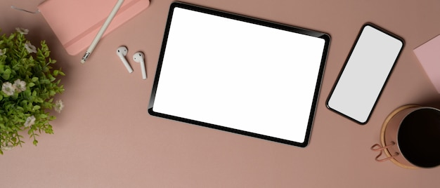 Top view of blank screen tablet and smartphone on pink table with stationery and accessories, clipping path.