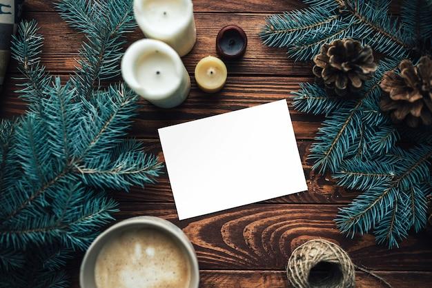上面図クリスマスツリーの枝と木製のテーブルの上の空白の紙