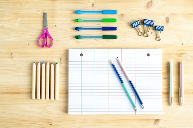Top view of blank sheet of paper, some clips, pencils, highlighters, pens and scissors on wooden table