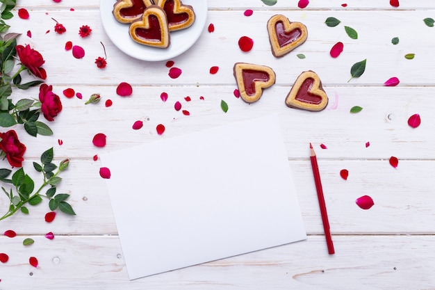 Top view of a blank sheet of paper on a wooden table with cookies and roses on it