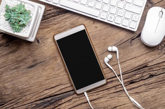 Top view of blank smartphone,  earphones, keyboard and mouse on grunge wooden desktop.
