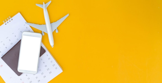 Top view on blank smartphone with passport and calendar and airplane model on yellow background