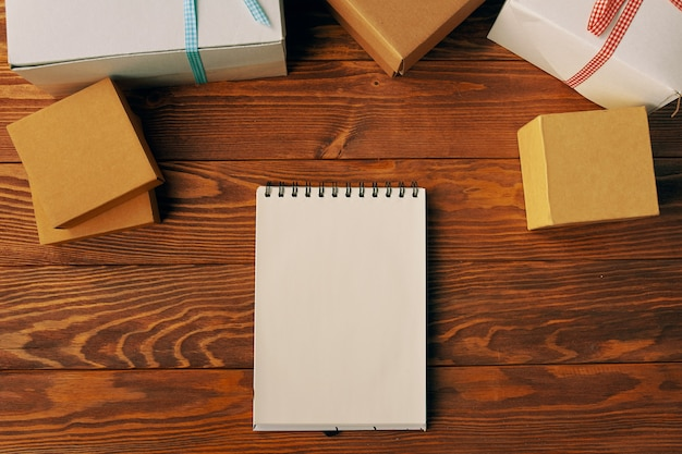 Top view of blank spiral bound notebook and gift boxes on wood table background business desk minima...