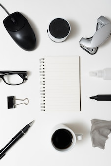 Top view of blank spiral notepad with office stationery; coffee cup; eyeglass over white desk