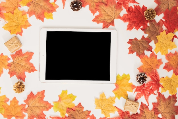 Top view blank  tablet decorated with colorful maple autumn leaves and gift boxes