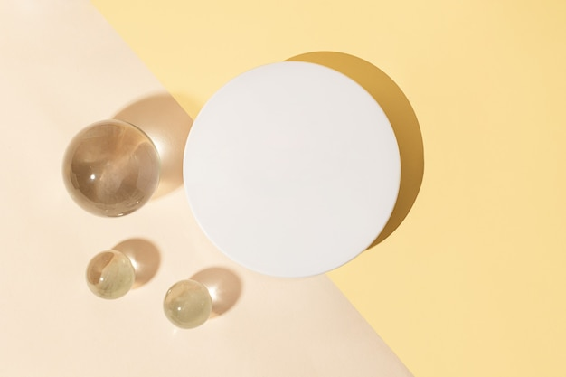 Top view of the blank white cosmetics box on the dual pastel backgroundglass sphers near it