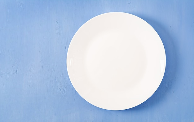 Top view of blank white dish on a blue background.
