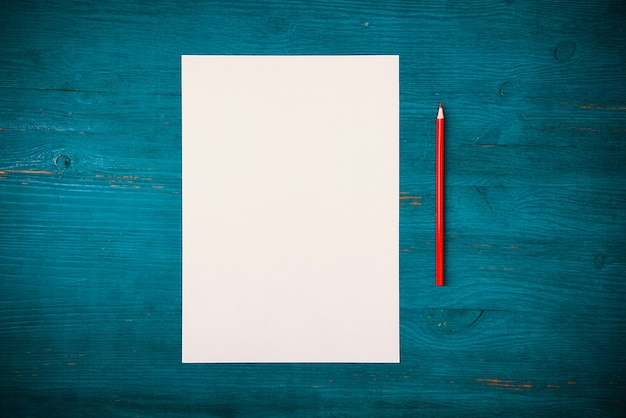 Top view blank white sheet and a pencil on textured blue wooden background