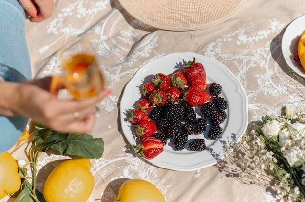 Вид сверху одеяло для пикника с разнообразием фруктов. затуманенное женщина рука бокал вина.