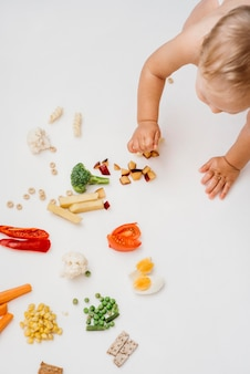 Вид сверху белокурый ребенок, выбирающий, что поесть