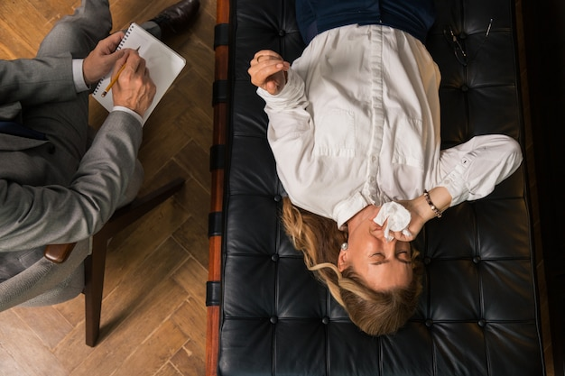 Top view of a blonde depressed woman shedding tears in the presence of her doctor during the therapy session