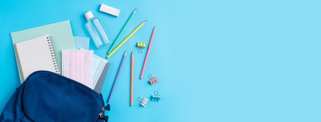 Top view of blue backpack with school stationery over blue table background, back to school design concept.
