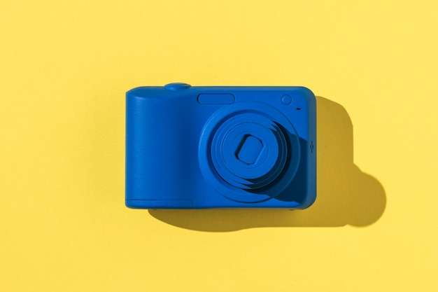 Top view of a blue camera on a yellow and pink background. stylish equipment for photo and video shooting.