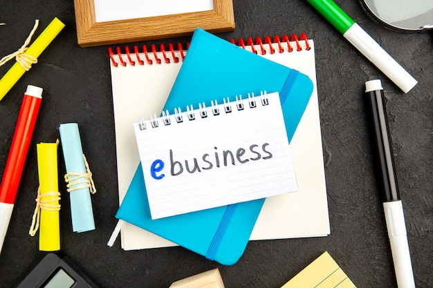 Il quaderno blu con vista dall'alto con matite colorate su superficie scura il disegno ispira gli affari del quaderno della penna del blocco note della scuola