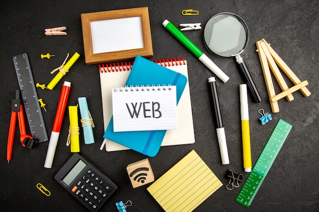 暗い表面の描画にカラフルな鉛筆でトップビューの青いコピーブックは、学校のメモ帳のペンのコピーブックのwebを刺激します