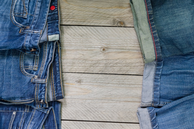 Top view of blue denim jeans arranged on wooden. beauty and fashion clothing concept