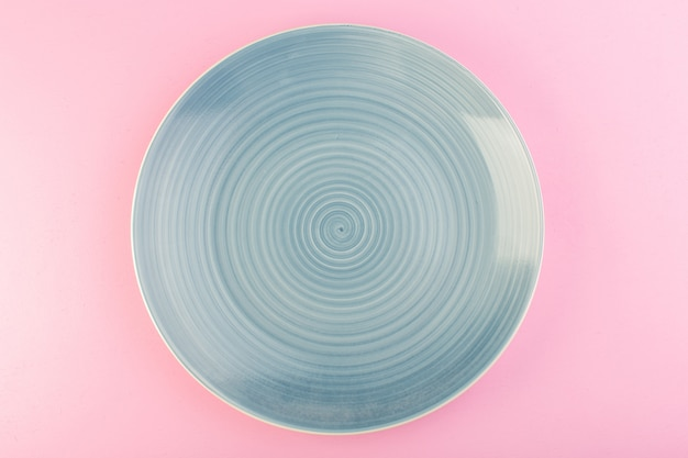 A top view blue empty plate glass made plate for meal on pink