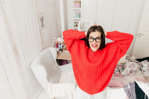 Top view of blue eyed, brunette young female in casual red sweater, wears rectangular spectacles, stands in her spacious room at home