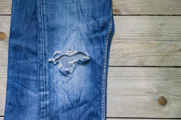 Top view of blue faded jeans with a hole on wooden surface. beauty, fashion and shopping concept.