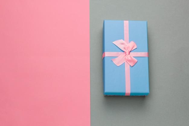 Вид сверху синяя подарочная коробка с праздничным розовым бантом на сером фоне в пастельно-розовой рамке со свободным пространством для текста