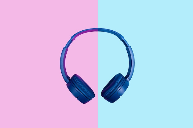 Top view on blue headphones on two colored background. flat minimal style. design and colors